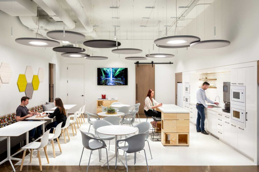 An employee kitchen space is a clean white break with marble topped island and four top tables.
