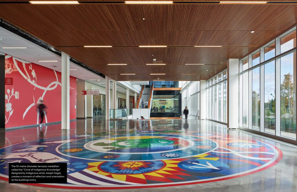 """A 10 meter terazzo medallion called """"Circle of Indigenous Knowledge"""" designed by Indigenous artist Joseph Sagaj creates a moment of reflection and orientation at the building's entry."""