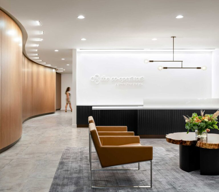 Reception area at the Cooperators Regina has a cool slate carpet and a curved wood wall lined across from the black-clad reception desk.