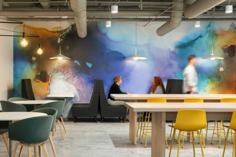 The employee cafe area at the Cooperators Regina has a watercolour inspired accent wall, booths, four top tables as well as long harvest tables.