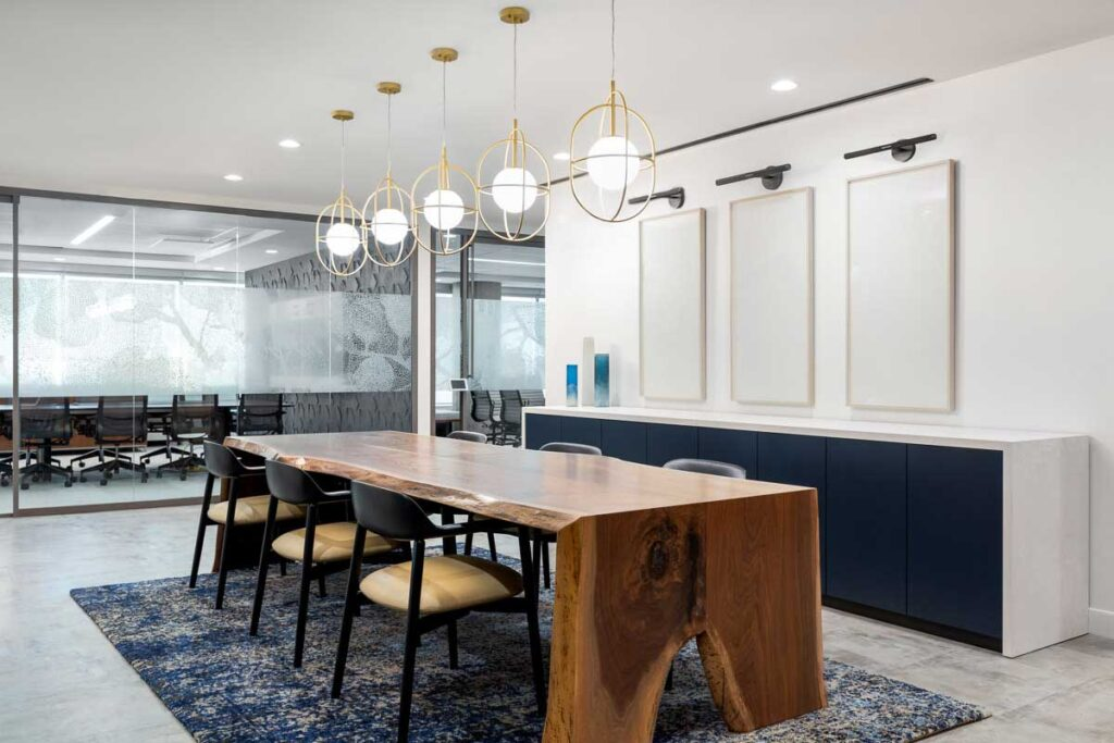 A meeting area at the Cooperators Regina office has a live edge wood table with gold wire pendants overhead.