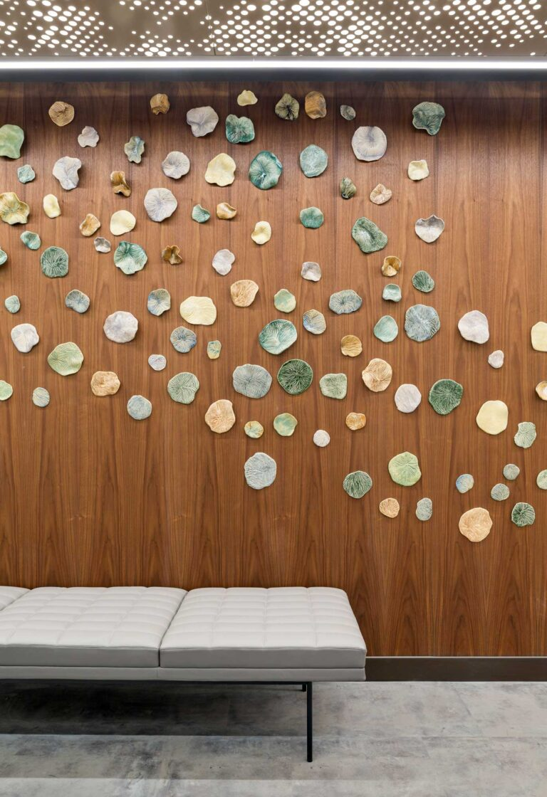 Close up of ceramic installation that sweeps across the wood panelled wall at the Cooperators Regina office.