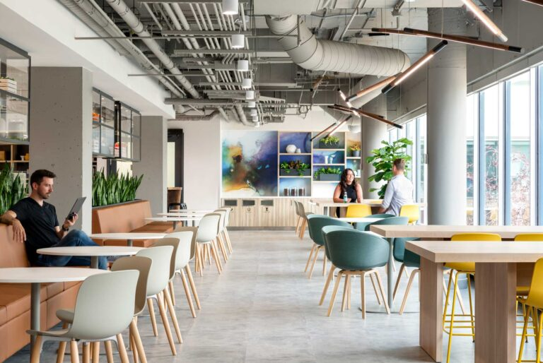 The employee cafe space is bright and airy with light wood tables, plants and a wall of windows.