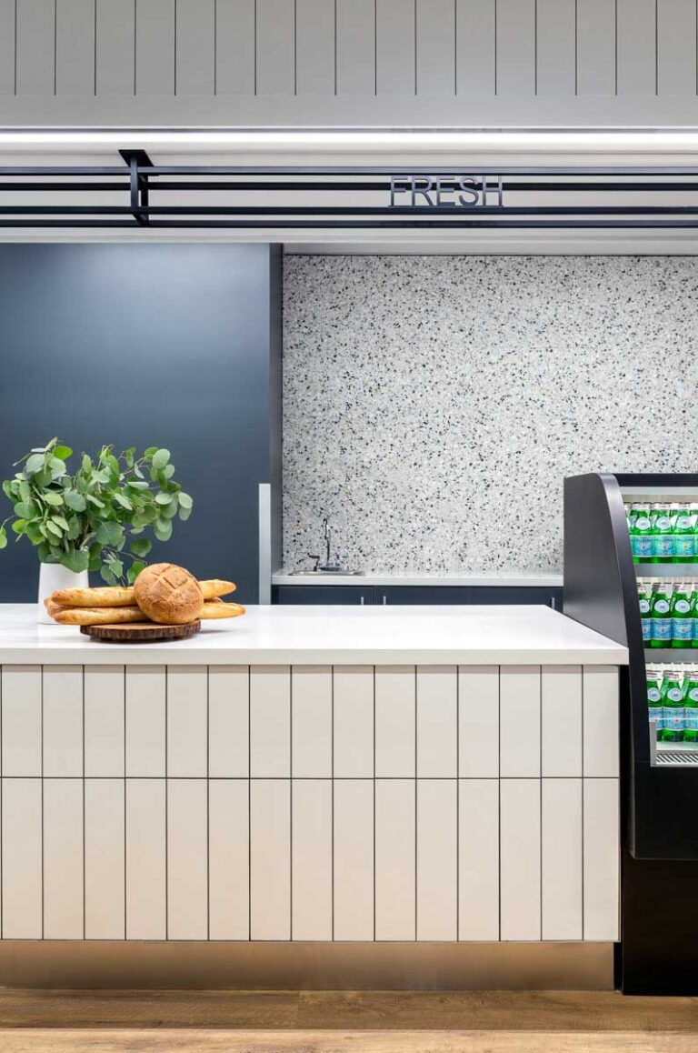The employee cafe area has a white marble counter and an accent wall in a black and white speckle.