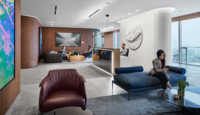 Behind the reception desk at First Gulf is a textured round sculputre which compliments the textured white wall nearby.