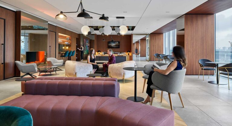 Employees gather in the First Gulf cafe space with cosy seating, wood panelled walls and a modern circular light fixture.