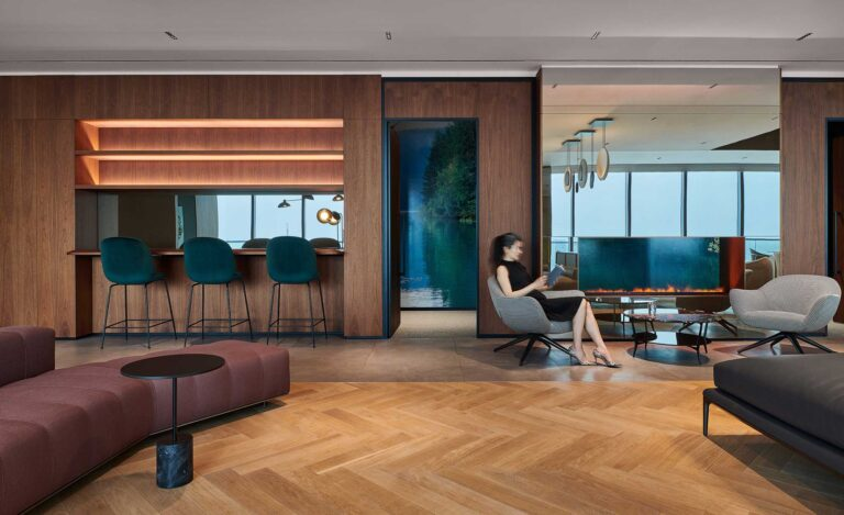 A woman sits in the employee cafe space with herringbone wood floors, and cushy seating at First Gulf office.