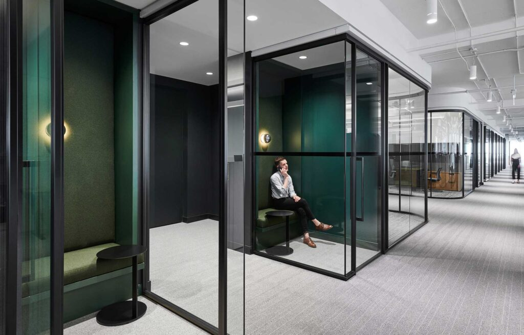 An employee chats in a closed office phone booth with dark, emerald walls and glass wall in a black frame.
