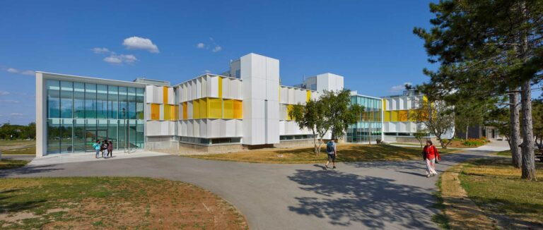 A path leads to an accessible entrance of the A wing Fleming College, with the glass walled window next to the newly clad orange and white wing.