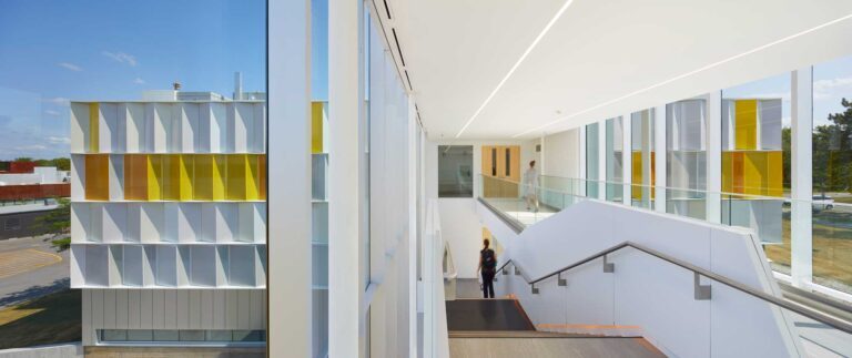 A staircase leading down provides a view of the L shape of the building up ahead with its bright white and orange panelling.