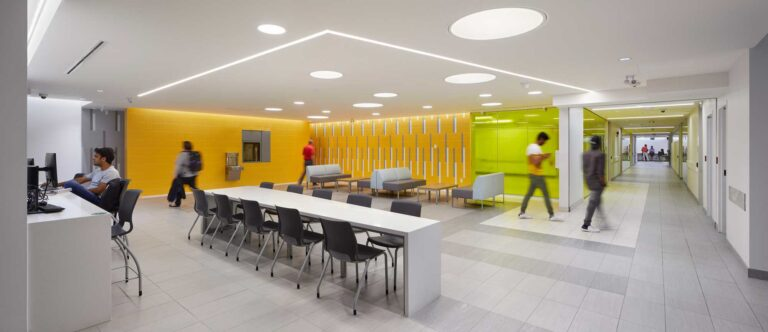 Students pass through a study space lined in bright tangerine at Fleming College.