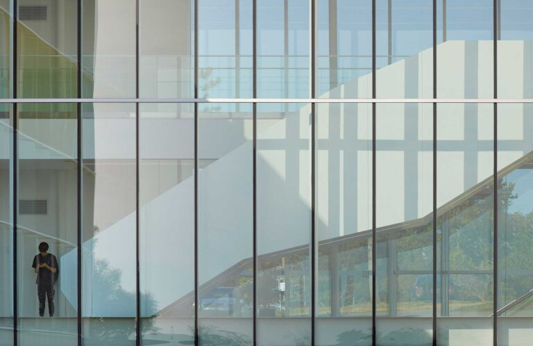 Exterior view of a white staircase connecting two floors, seen through the glass walls of the A wing, Fleming college.