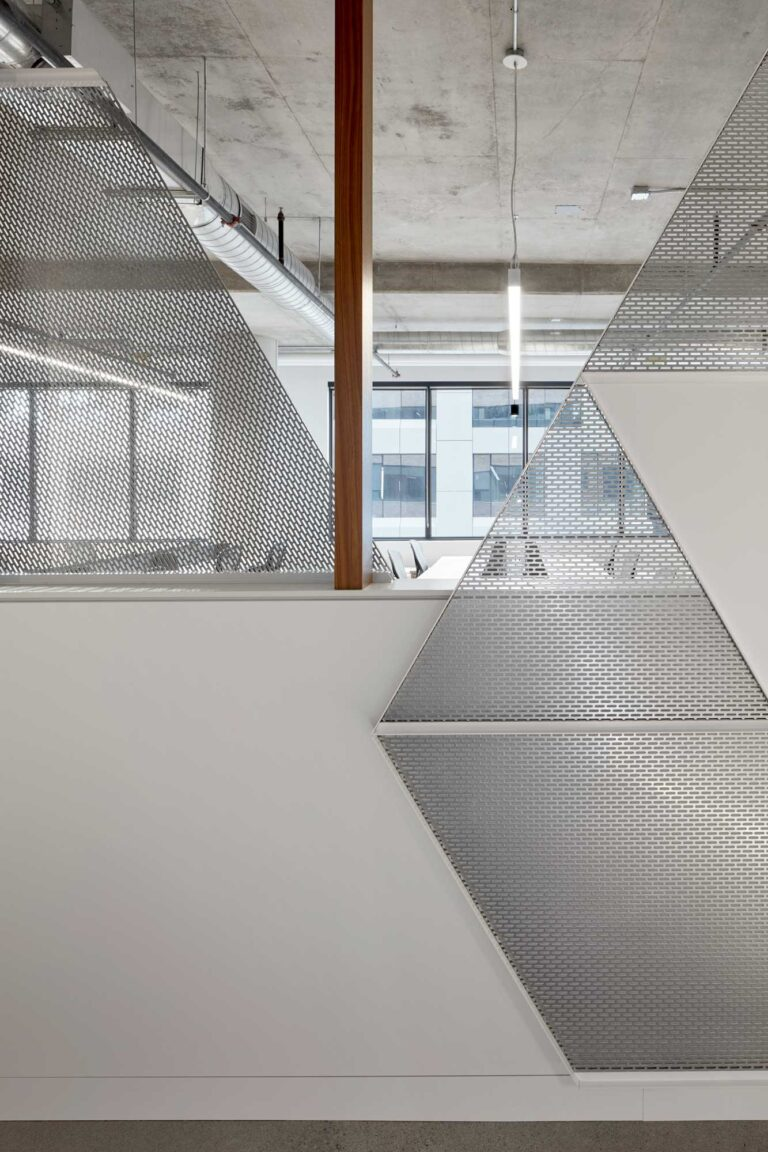 A divider between office space and corridor at Red Bull Canada with triangular perforated silver screens