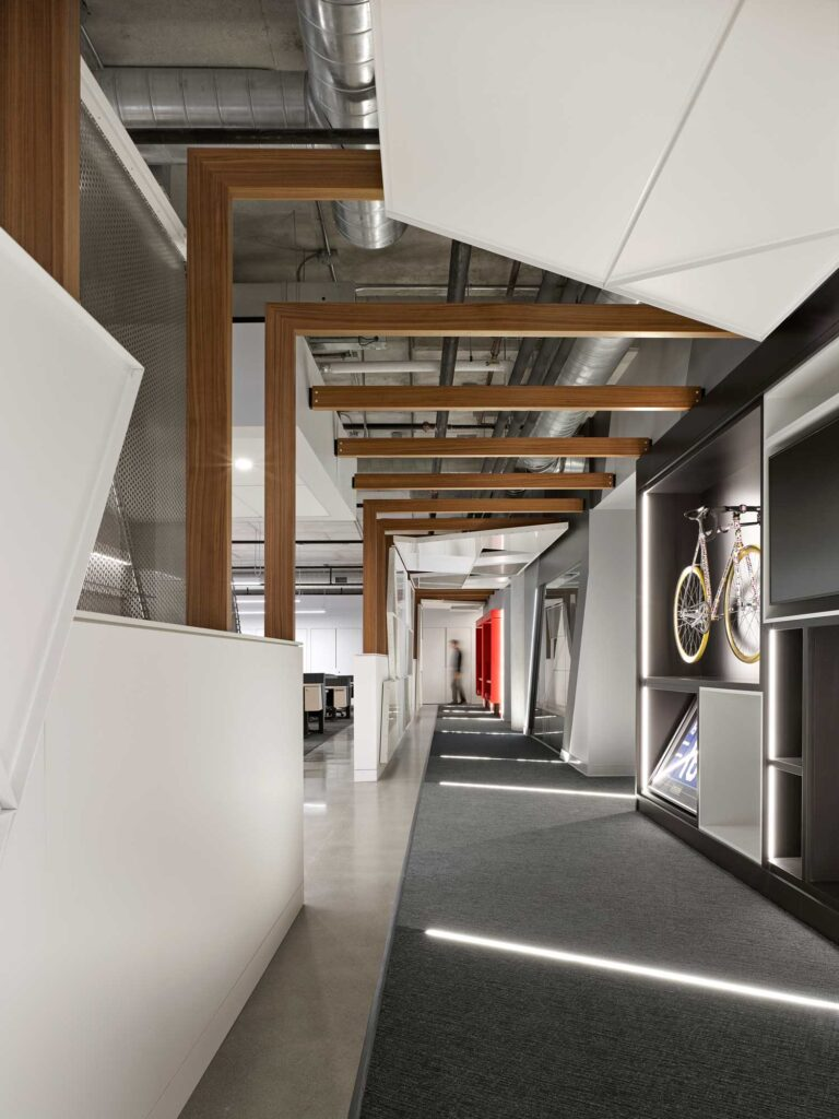 """The corridor dubbed the """"Vortex"""" at Red Bull Canada has wood beams overhead and company memoribilia inset in vignettes."""