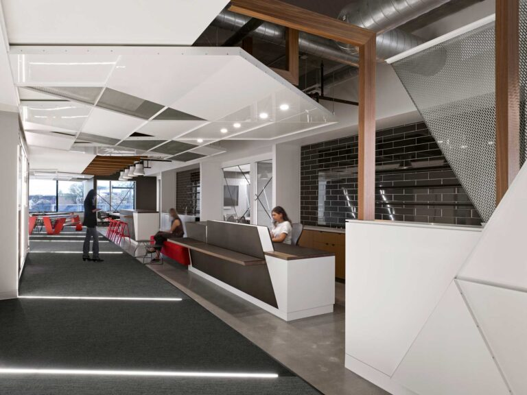 The reception area at Red Bull Canada has a long white reception desk with wood countertop and wall lined in black tiles behind.