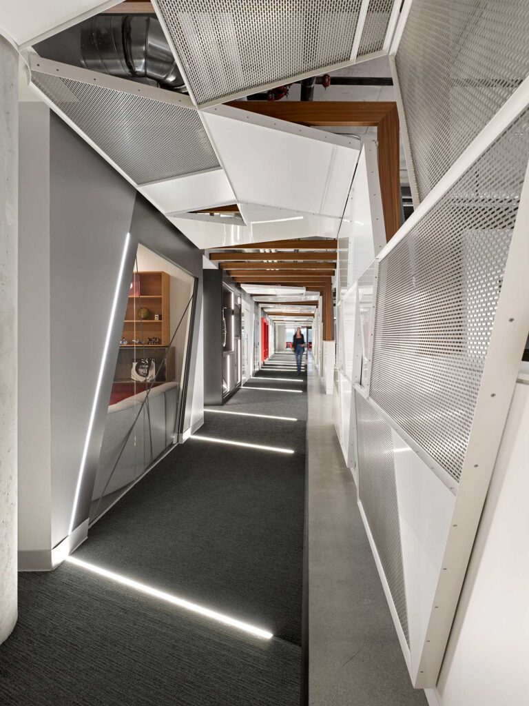 Corridor at Red Bull Canada with perforated metal screens in geometric shapes framed in white.
