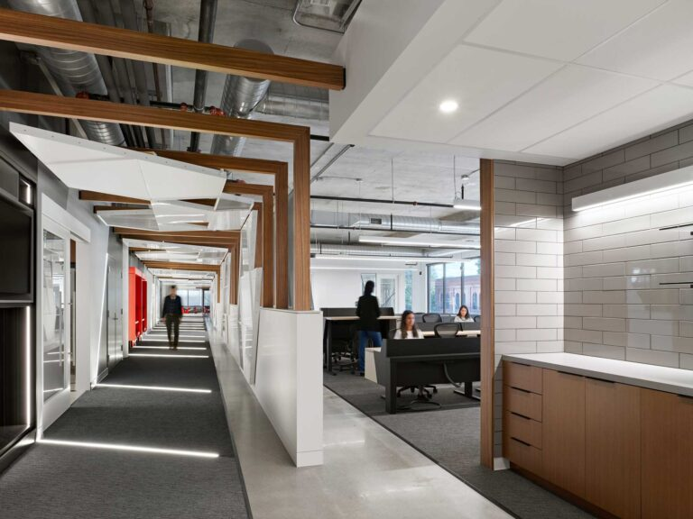 The long corridor at Red Bull Canada is lined with wood beams and white panels in geometric shapes.