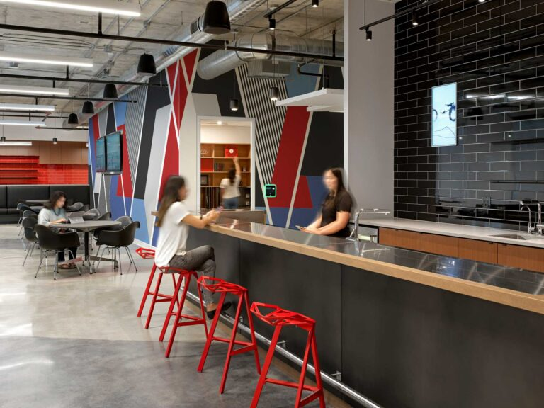 Employees gather in the cafe space with black tiled walls and a geometric mural in red, blue and black.