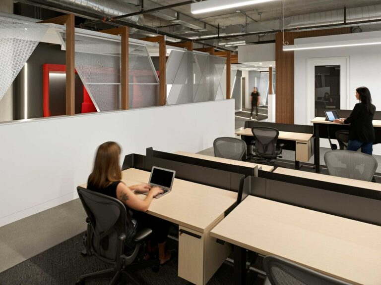 Staff work in the adaptable workspace at Red Bull Canada with pale wood sit-stand desks and a view of the adjacent corridor.