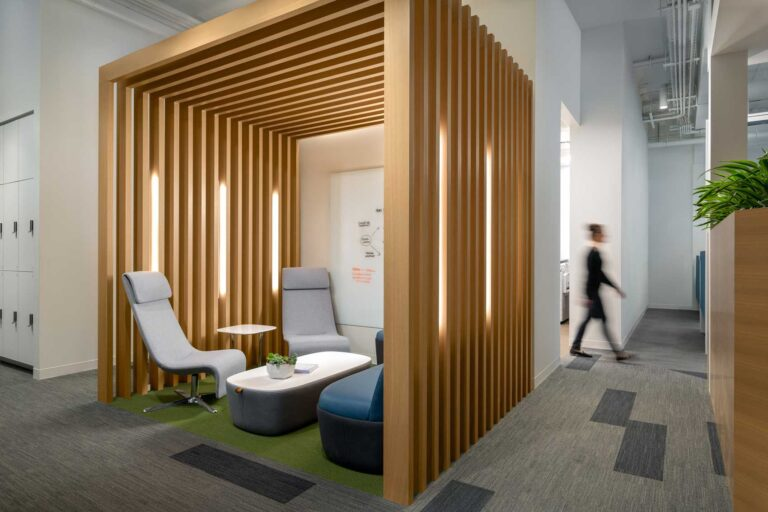 A meeting area becomes a cozy nook with a slatted box overhead.