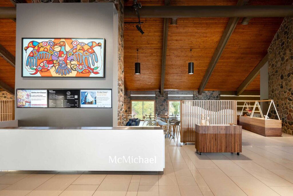 A painting in the Woodland style sits over the Corian clad reception desk at the entrance of the McMichael Canadian Art Collection.