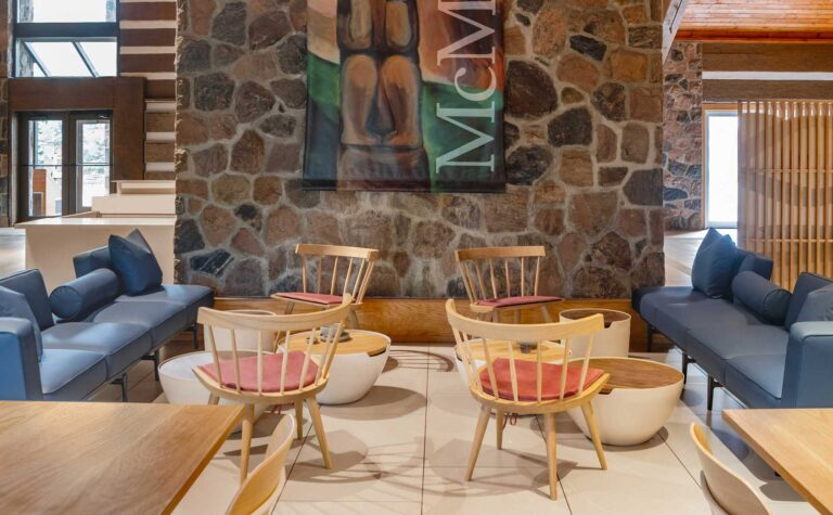 Wooden chairs are placed opposite blue sofas in the cafe of the McMichael Canadian Art Collection.