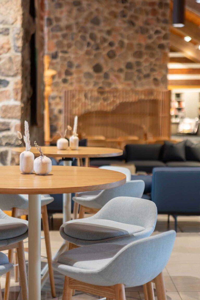 A high top table with low backed gray chairs provides a spot to perch over coffee at the McMichael Canadian Art Collection.