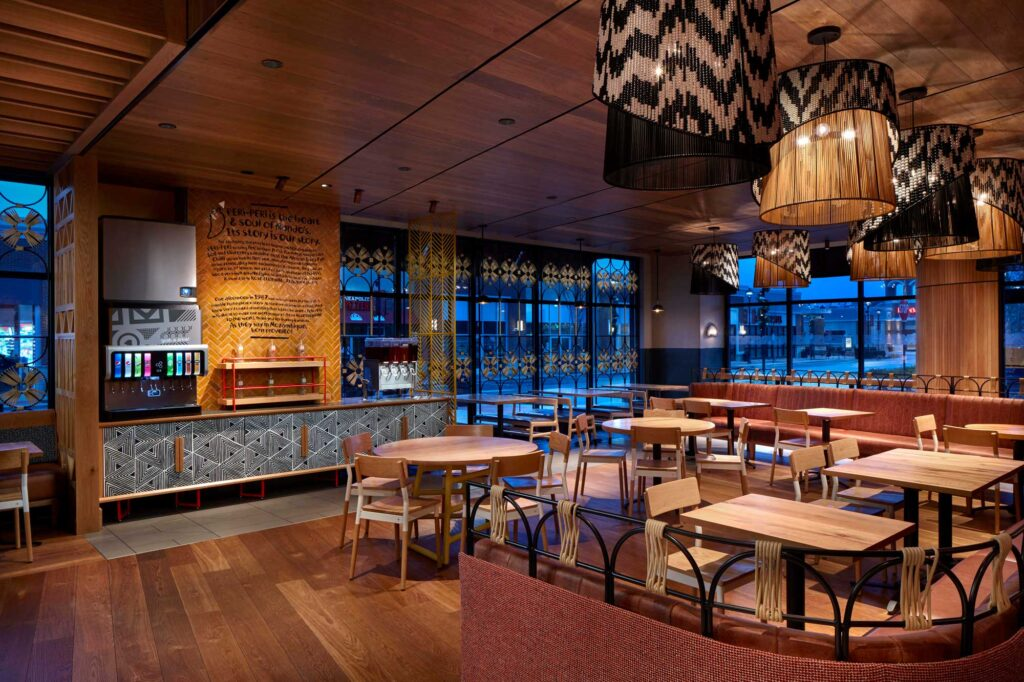Beaded lampshades introduce the South African patterning and demarcate the seating area at Nando's Woodmore.