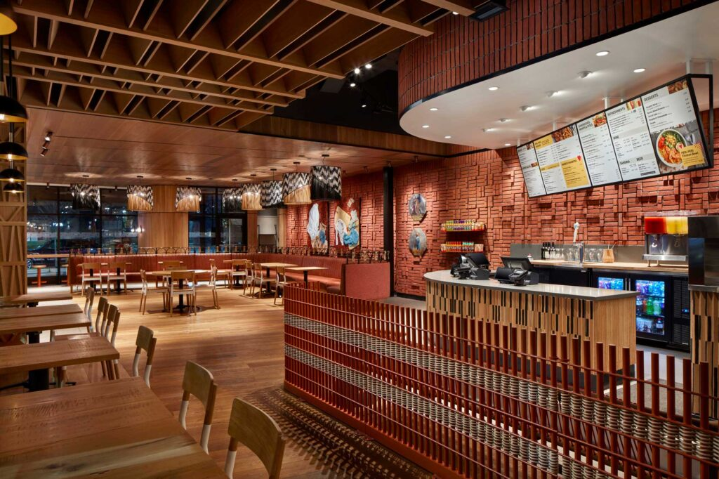 View of the entry at Nando's woodmore, a textured wall decorates the takeout counter and digital screens display the menu.