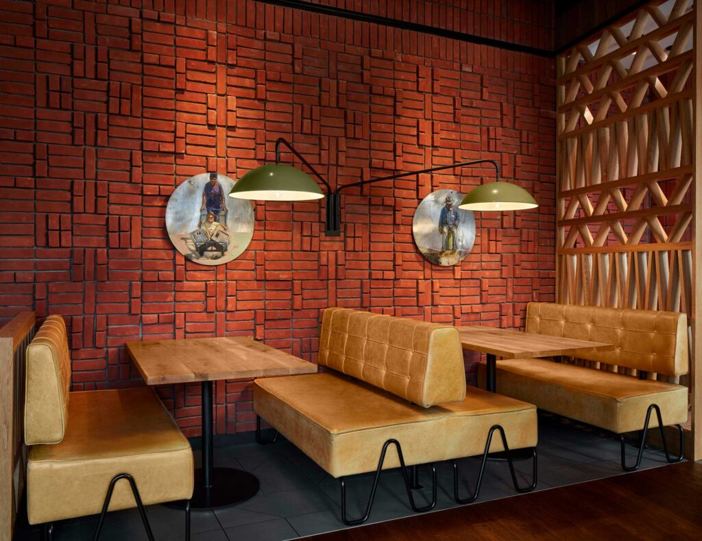 Camel coloured leather booths are set against a brick wall to offer seating options at Nando's Woodmore.
