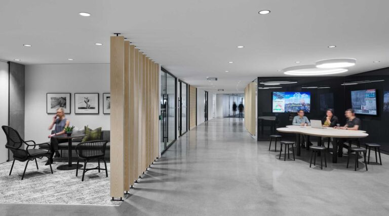 At OPG offices, staff are seated at a casual meeting table, across the hall from a semi enclosed meeting space demarcated by slat dividers.
