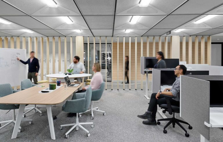 A team works together in an office with workspace options grouped around a meeting table with sit and stand options.