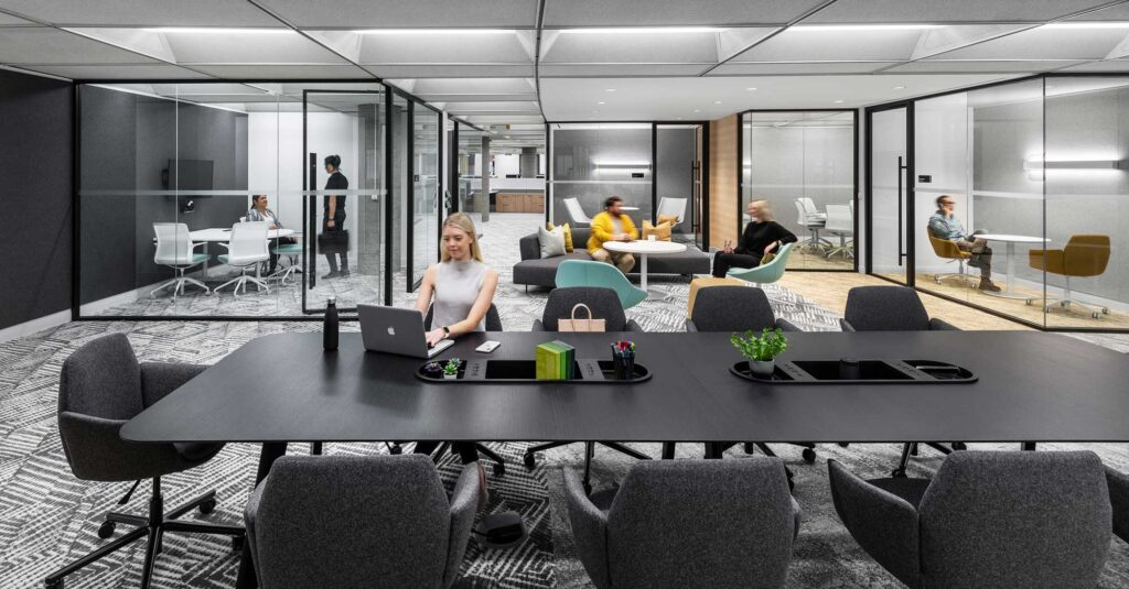 Staff work in the OPG office with a black and white patterened carpet, glass enclosed meeting rooms and a large table for work or meeting space.