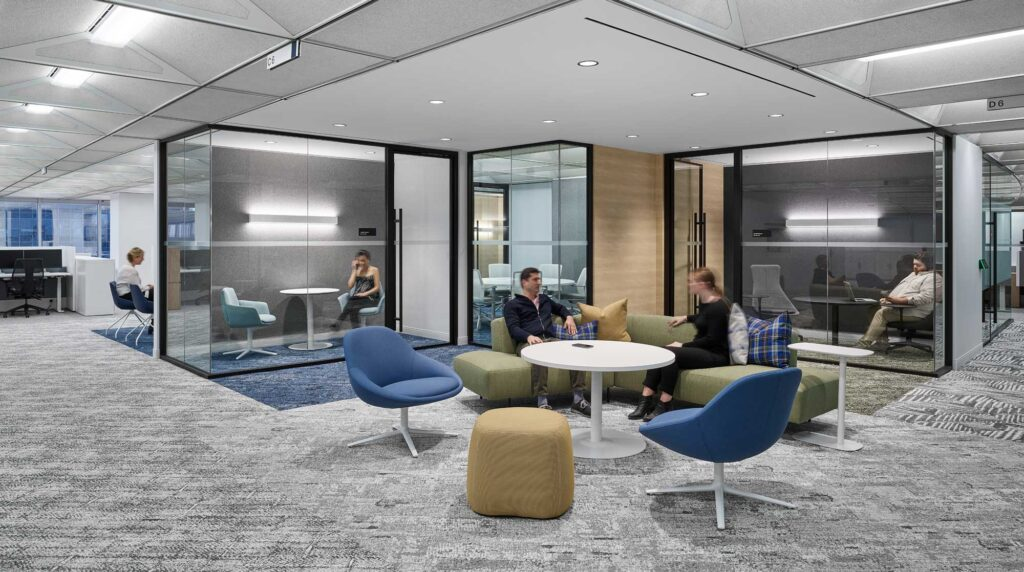 Meeting rooms provide quiet space to take a phone call, while outside, staff have a couch seating options in yellow, blues and golds.