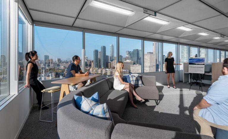 Staff work together in an open presentation area with long sectional sofa, high top tables and breathtaking city views.