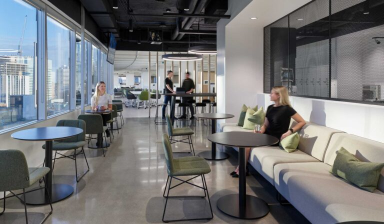 An employee cafe provides space to eat as a duo or along a long booth with city views in behind.
