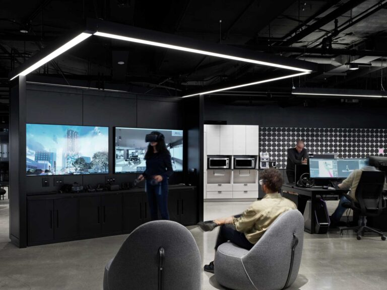 A woman uses a VR headset in the Smart City Sanbox in a room with a black console with TV screens and a polished concrete floor.