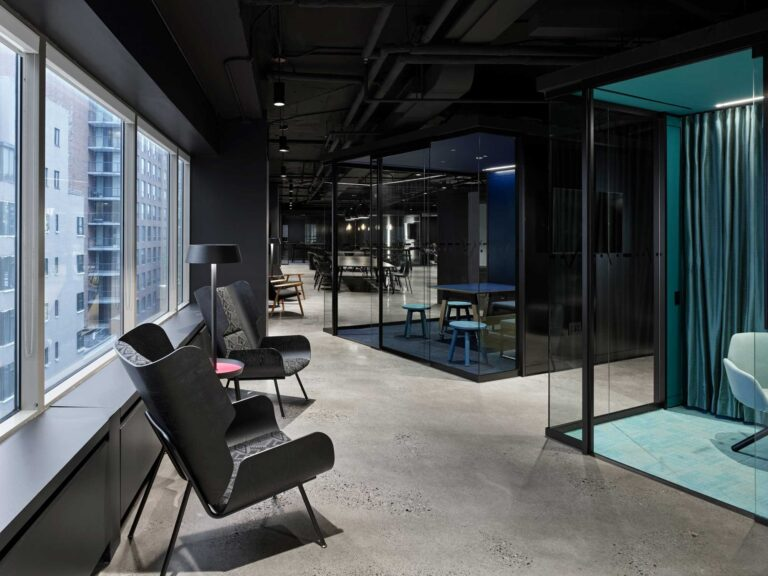 Along the windows of Smart City Sandbox, two lounge chairs face indivdual jewel box phone rooms.