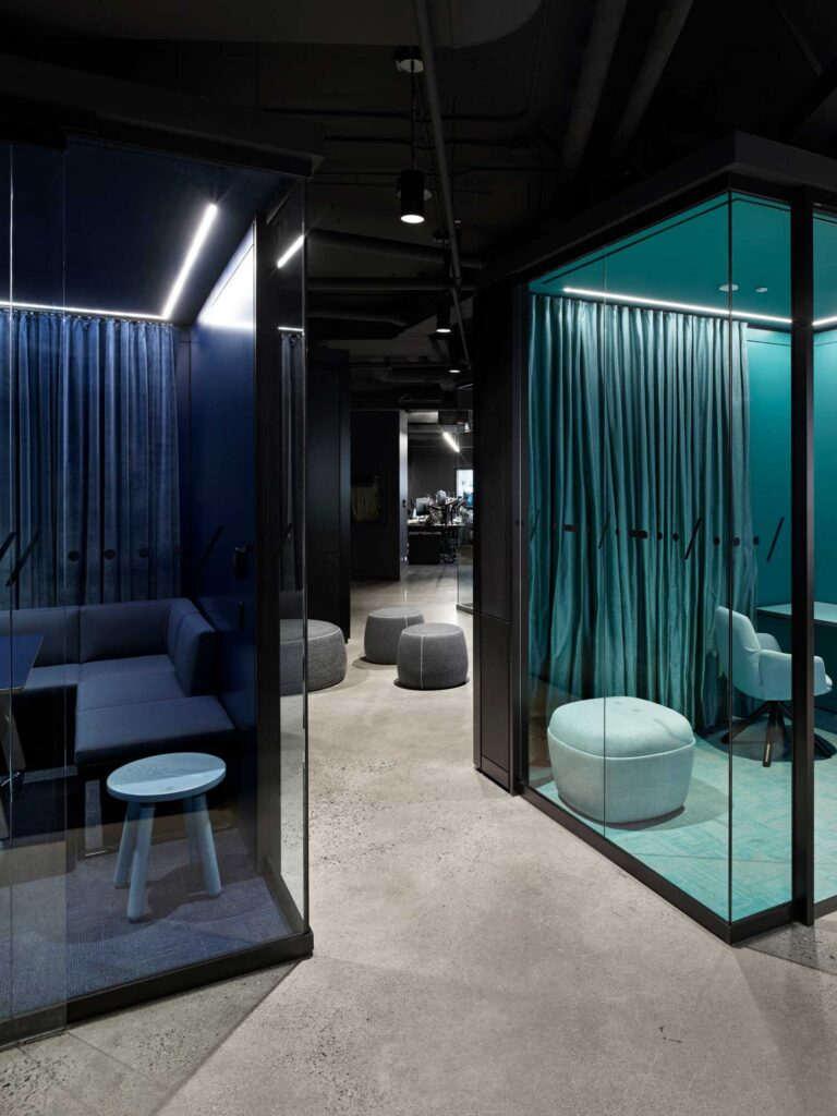 Two private meeting rooms sit on a polished concrete floor, each monochromatic in lapis blue and teal, respectively.