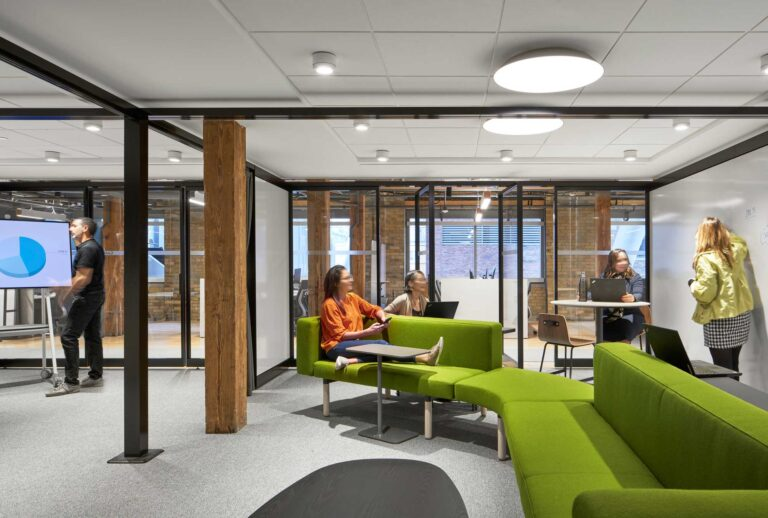 Staff in a meeting room make use of high-top tables, and a bright green sofa with adjacent end tables.
