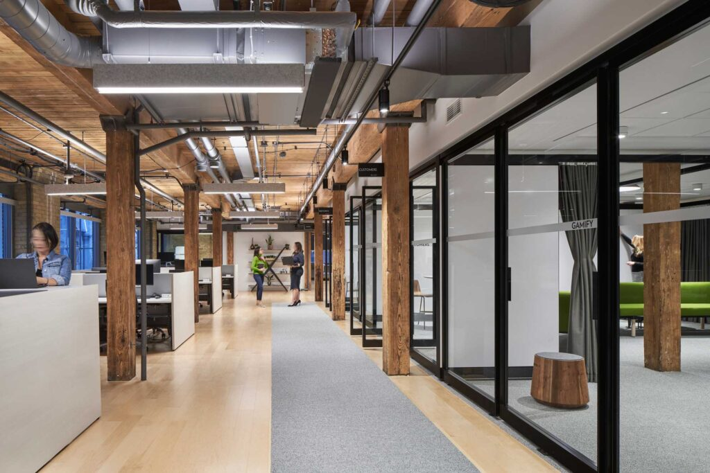 A corridor at Sobey's Innovation Hub, showcases the original beams of the building and the glass walled meeting rooms and workspace options.