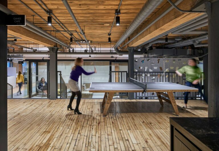 Two staff play ping pong in the Innovation Hub with the original wood floors and ceilings overhead.