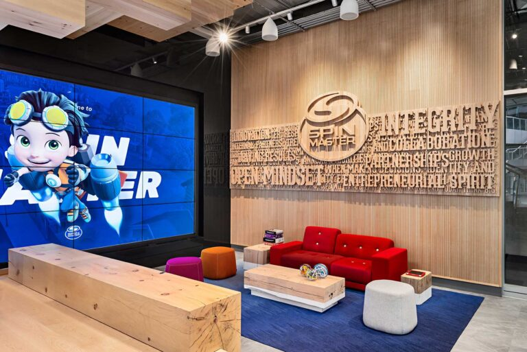 A waiting area at Spin Master has a feature wall with company values engraved in wood next to a screen emblazoned with company branding.