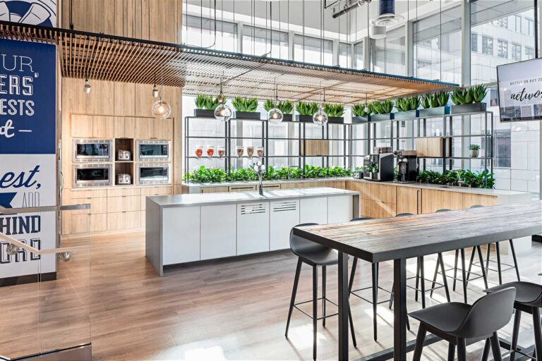 The employee cafe space is lined in pale wood and plants, with a tambour wood installation overhead.