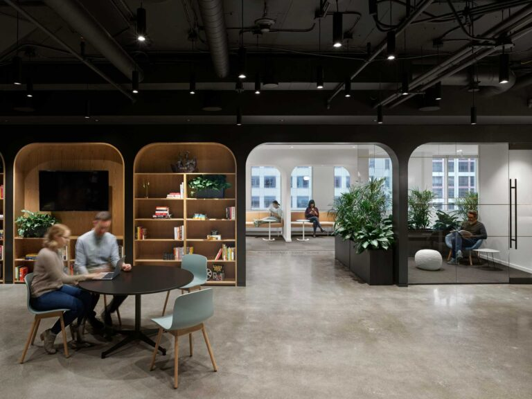 Two employees meet at a round black table in an open space a Spin Master 7th floor with polished concrete floor.