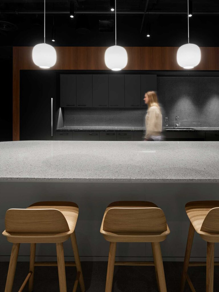 Cafe space at Spin Master 7th floor office with pale slate counter top, and three white pendant lights overhead.