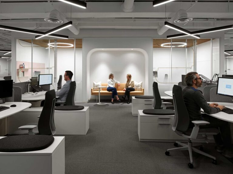Employees work in the 7th floor Spin Master office with white walls, desks and light fixtures overhead in the shape of X