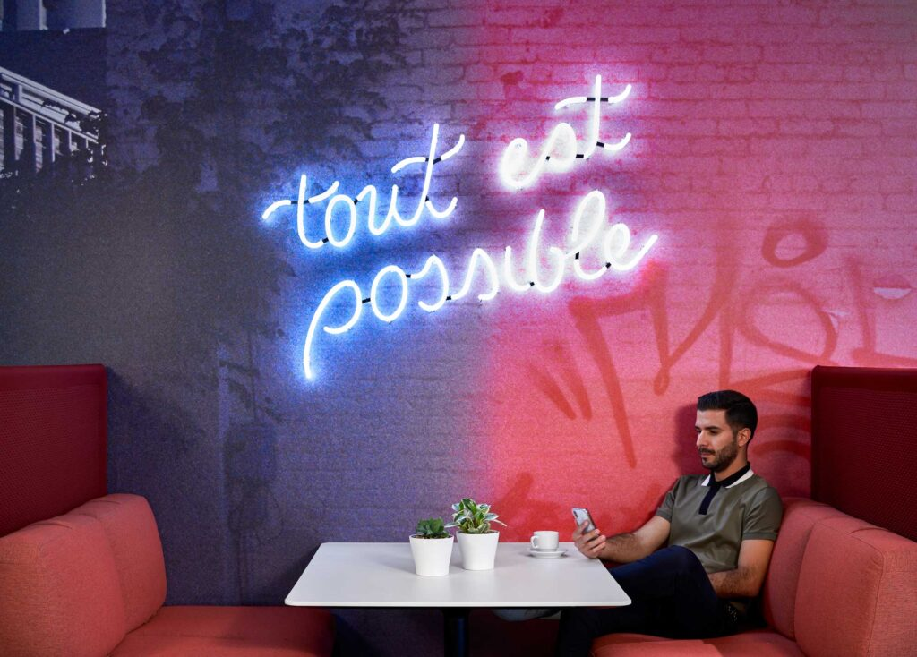 """A man looks at his phone while seated at a pink and red booth under a neon sign which reads """"Tout est possible""""."""