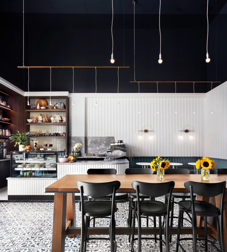 Harvest Table in a sleek cafe with black chairs and decked with sunflowers.
