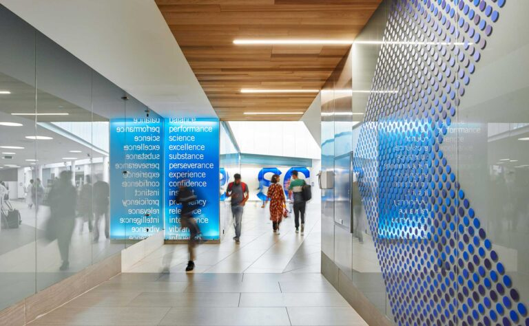 Students walk through the sleek corridors at Niagara College Student Commons with glass walls and a wood soffit ceiling overhead.